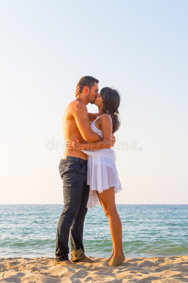 Young couple kissing at the beach royalty free stock photo