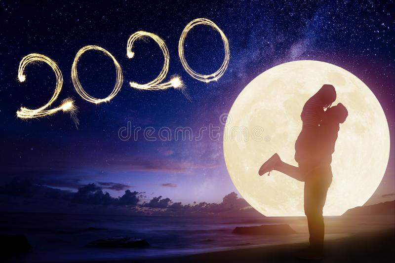 couple kissing on beach and watching the moon.Celebrate new year 2020 concept stock photo
