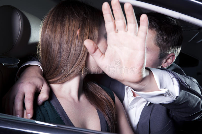 Young couple kissing in car at a red carpet event, man is shielding with his arm outstretched blocking paparazzi photographers royalty free stock photos