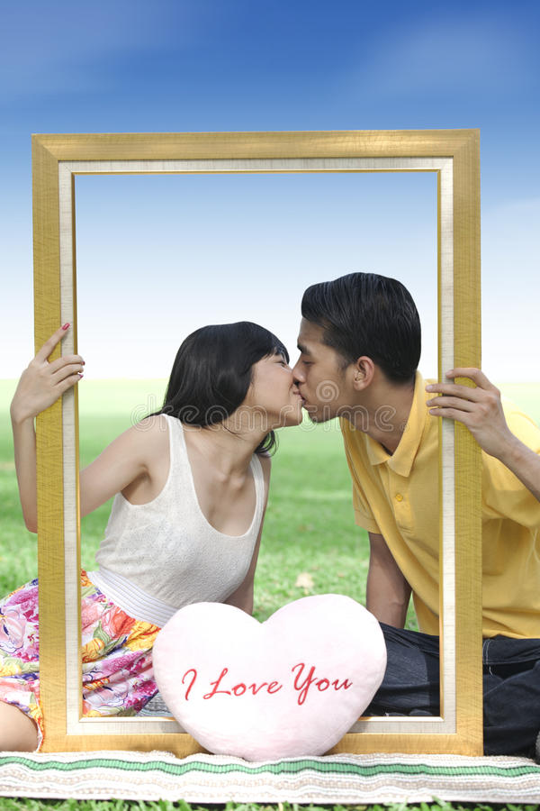 Download Young Couple Kissing With A Frame Stock Photo - Image: 22902000
