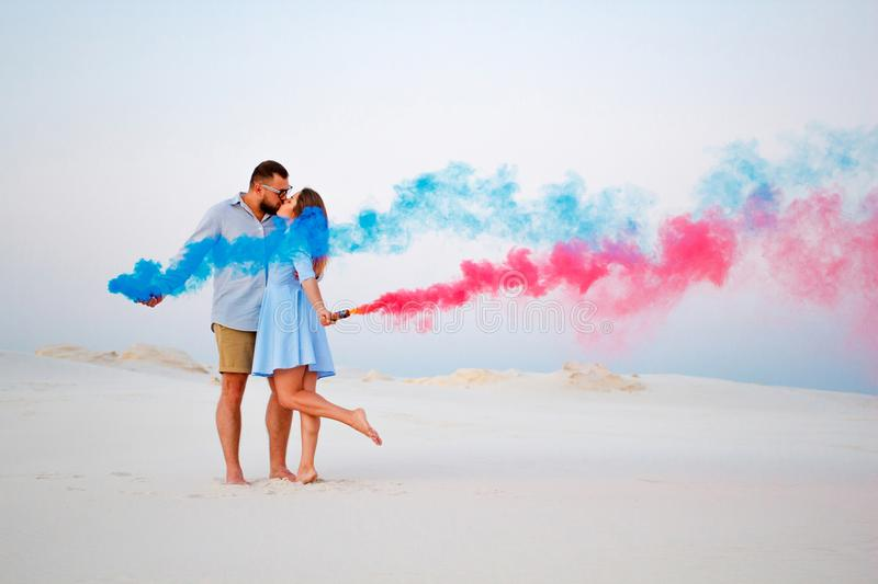Young couple kissing and holding colored smoke in hands, romantic couple with blue color and red color smoke bomb on beach.  stock photos