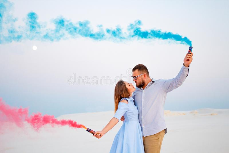 Young couple kissing and holding colored smoke in hands, romantic couple with blue color and red color smoke bomb on beach. Young couple standing on a sand and royalty free stock photos