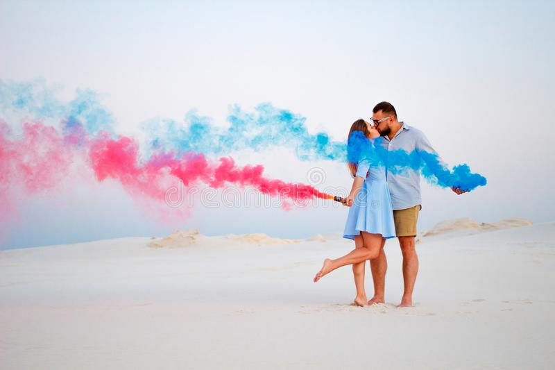 Young couple kissing and holding colored smoke in hands, romantic couple with blue color and red color smoke bomb on beach.  royalty free stock photos