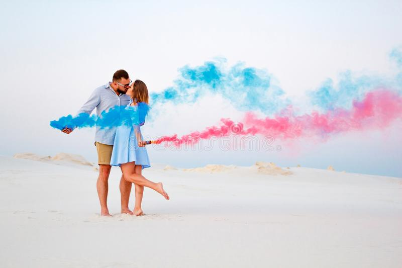 Young couple kissing and holding colored smoke in hands, romantic couple with blue color and red color smoke bomb on beach royalty free stock photos