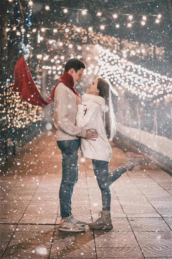 Young couple kissing and hugging outdoor in night street at Christmas time. Having fun together at a christmas fairy with snowfall stock photography