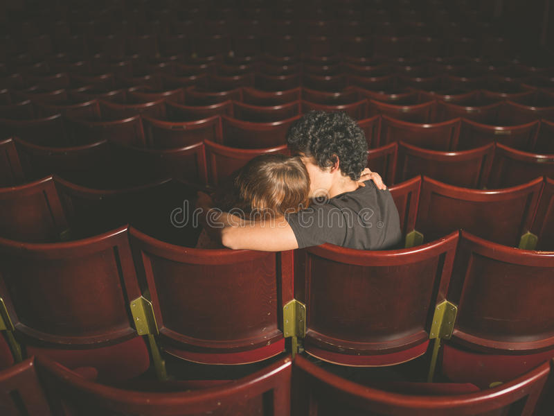 Young couple kissing in movie theater stock image