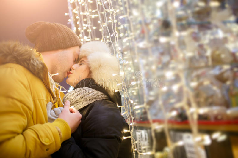 Young couple kissing at night. Romantic young couple kissing at night city among garlands royalty free stock images