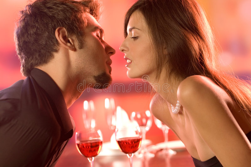 Young couple kissing in restaurant. Celebrating or on romantic date