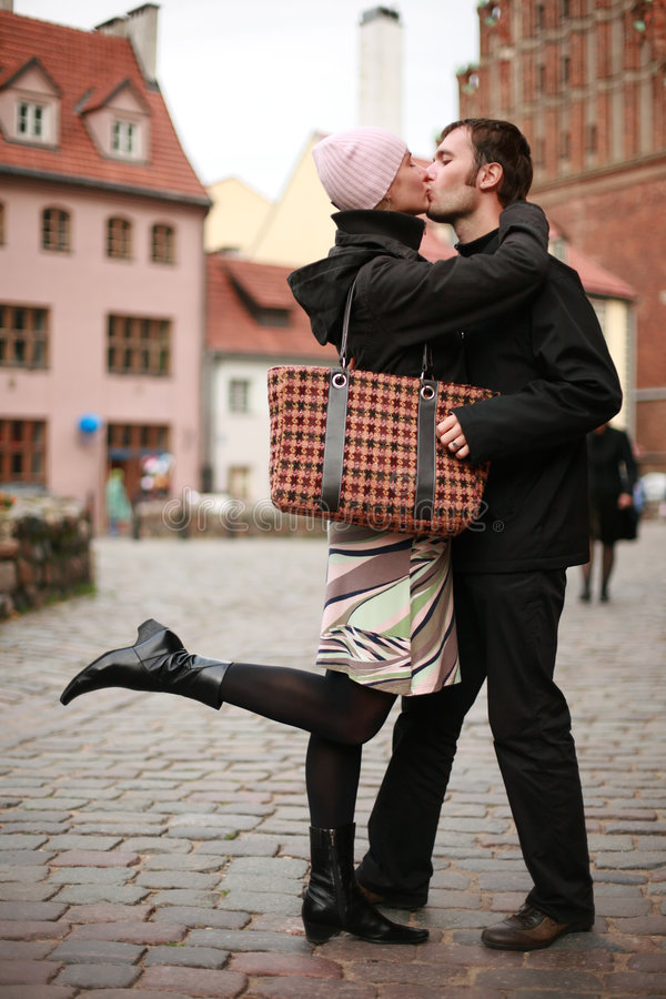 Young couple kissing in town. Young couple kissing in an old European town square stock images