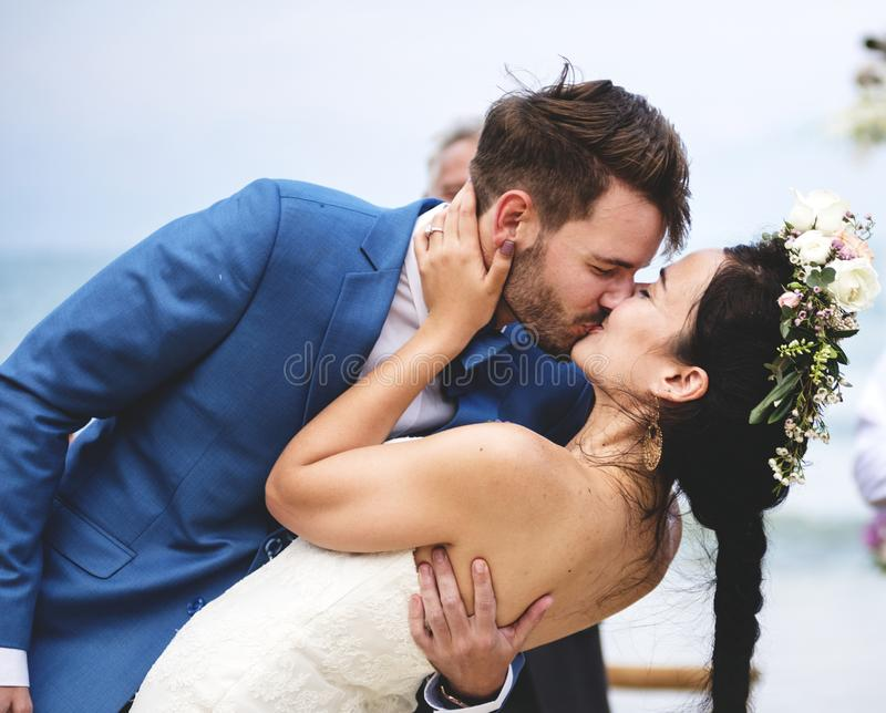 Young couple kissing at wedding reception stock images