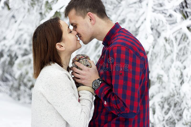 Young couple kissing in winter royalty free stock photo