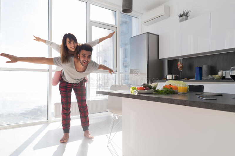 Young Couple In Kitchen, Lovers Hispanic Man Carry Asian Woman Modern Apartment royalty free stock photography