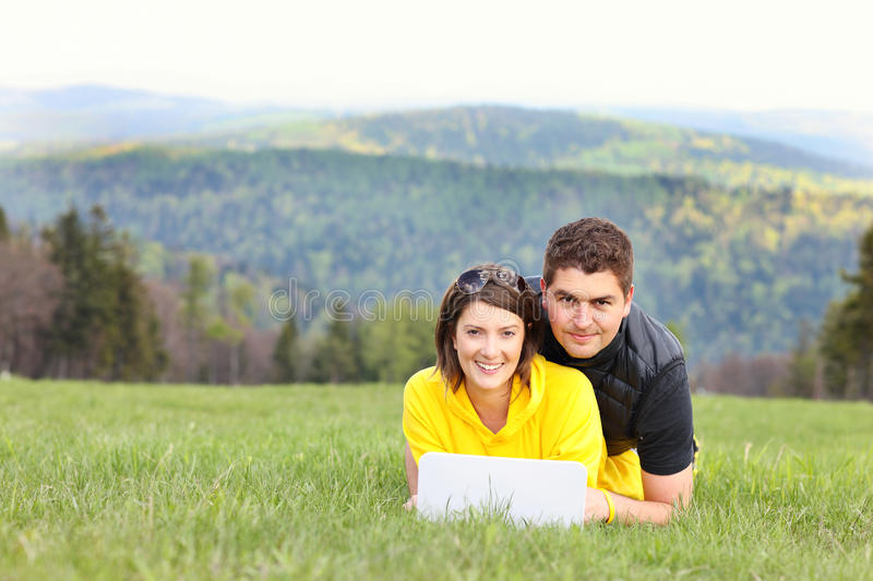 Young couple and laptop in the mountains royalty free stock photo