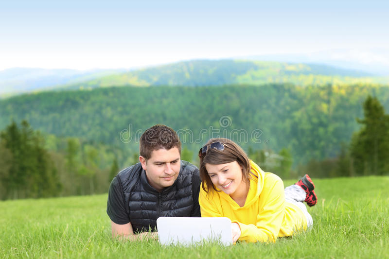 Young couple and laptop in the mountains royalty free stock photos