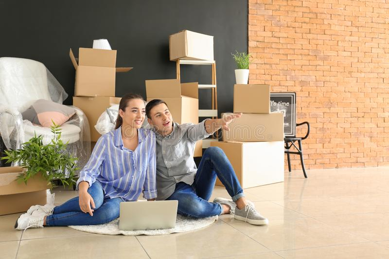 Young couple with laptop sitting on floor near boxes indoors. Moving into new house stock photo