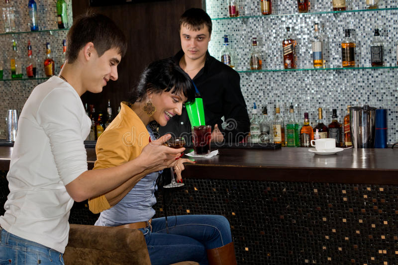 Young couple laughing as they drink at a bar stock photo