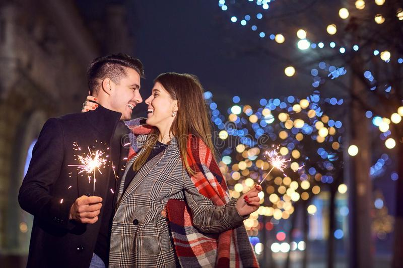 A young couple laughing with Bengal lights in the hands. stock image
