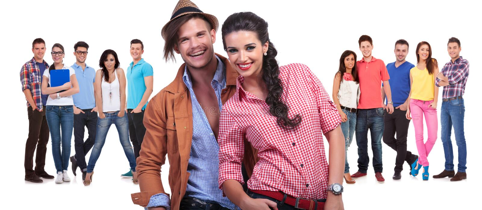 Young couple laughing in front of a large group of friends stock images