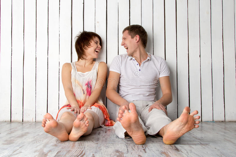 Young couple is laughing near the white wooden wall stock images