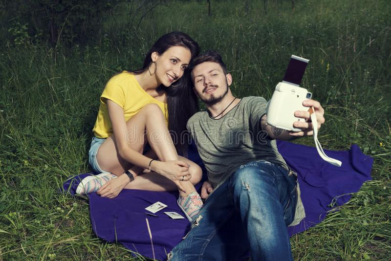 Young couple laying down on a purple blanket and taking photos selfie stock images