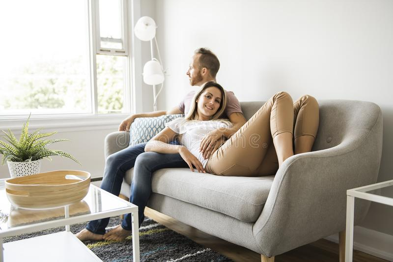 Young couple laying on the sofa relaxing at home royalty free stock image