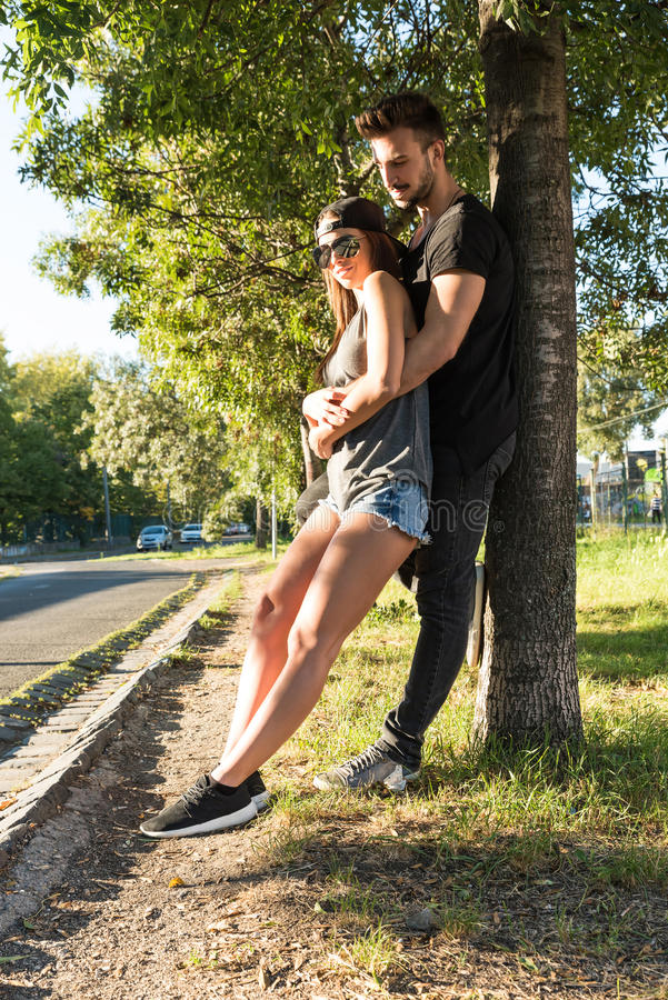 Young Couple leaning to a tree in a urban environment royalty free stock photos