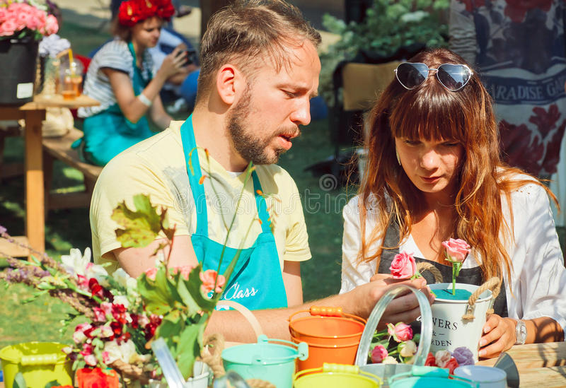 Young couple learns to make bouquets of flowers on the outdoor fair. KYIV, UKRAINE - JUL 23: Young couple learns to make bouquets of flowers on the outdoor fair royalty free stock images