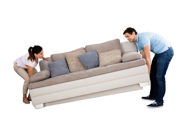 Young Couple Lifting Sofa royalty free stock photos