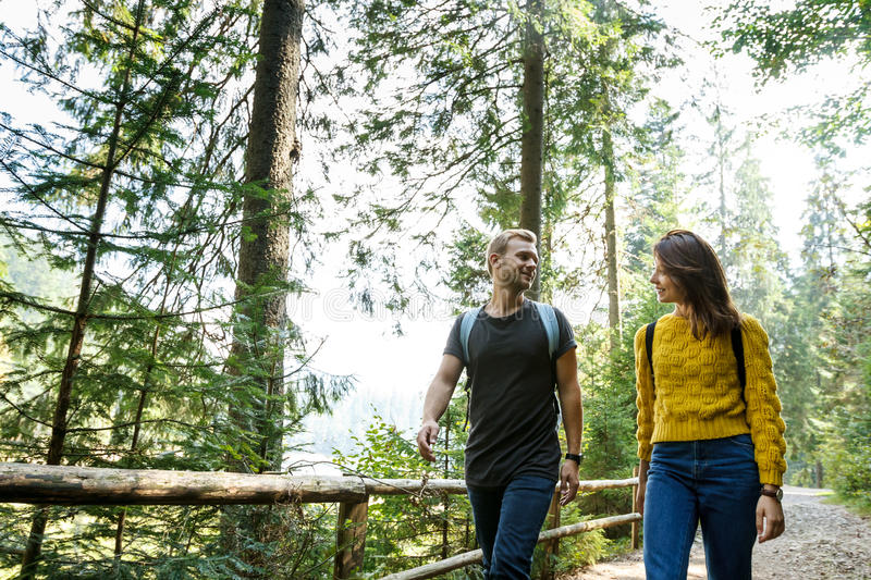 Young couple looking at each other, walking in mountains` forest. royalty free stock photography