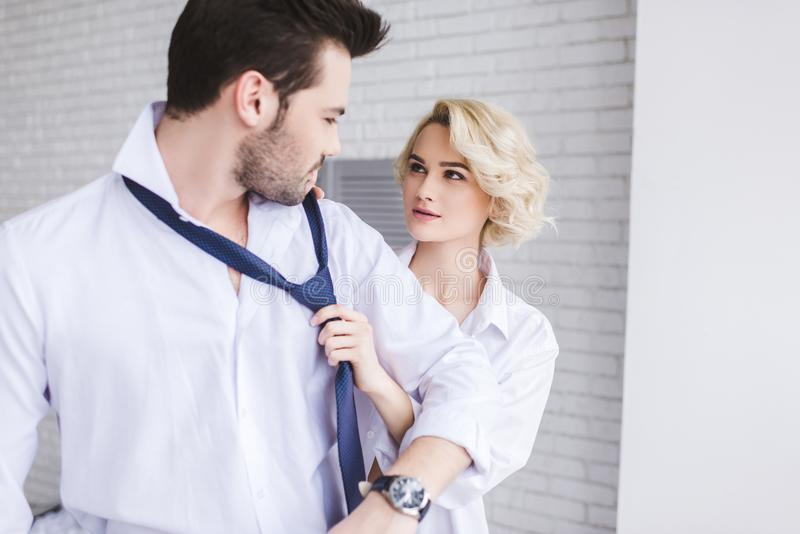 Young couple looking at each other while woman. Young couple looking at each other while women holding necktie of handsome boyfriend stock photos