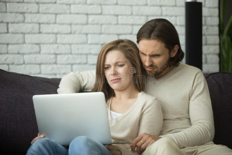 Young couple looking on laptop with disgust confused by news stock photography