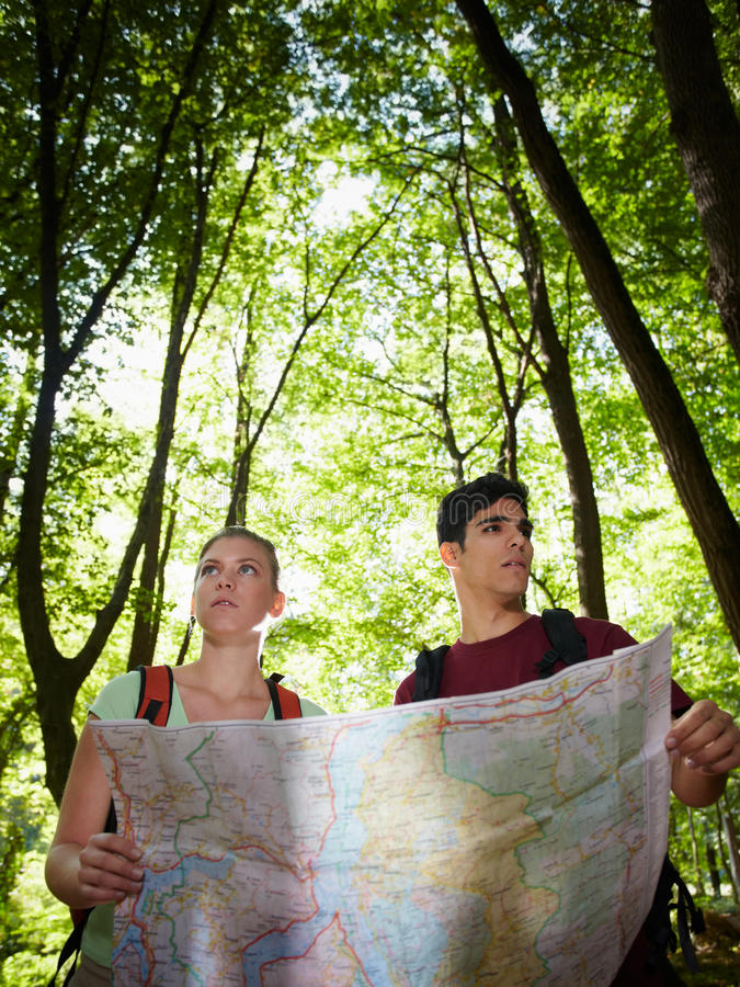 Young couple looking at map during trek stock images