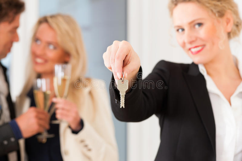 Young couple looking for real estate. Real estate market - young couple looking for real estate to rent or buy; they celebrate with champagne and get the keys royalty free stock photography