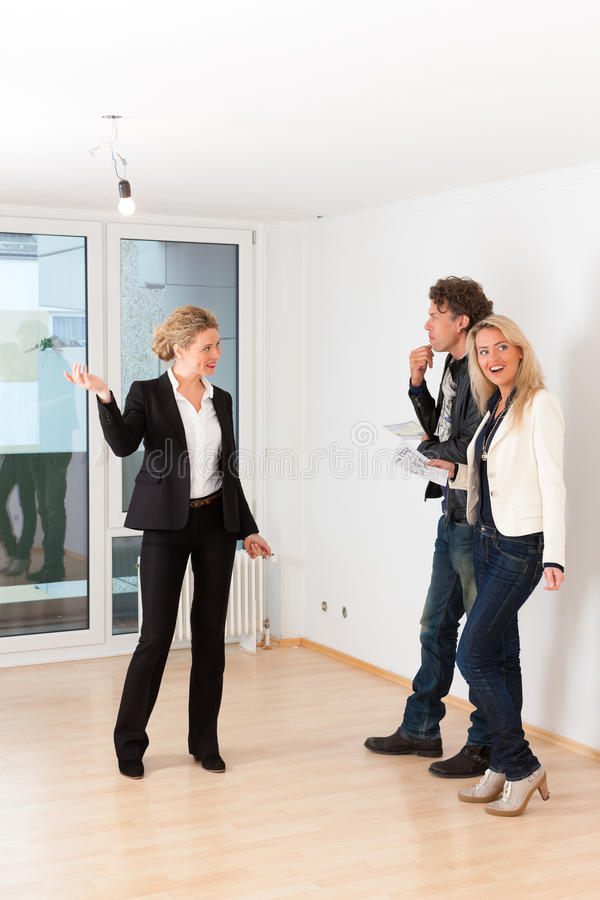 Young couple looking for real estate with female realtor. Real estate market - young couple looking for real estate to rent or buy an apartment royalty free stock photos