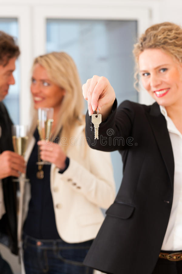 Young couple looking for real estate with realtor. Real estate market - young couple looking for real estate to rent or buy; they celebrate with champagne and royalty free stock photo