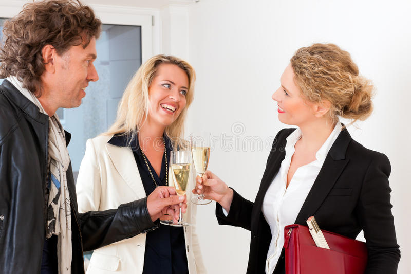 Young couple looking for real estate with realtor. Real estate market - young couple looking for real estate to rent or buy, they celebrate with champagne and royalty free stock photography