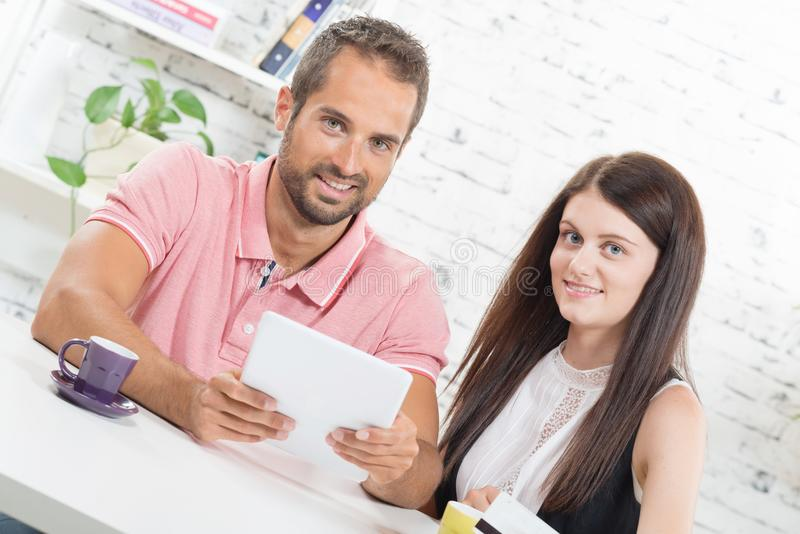 A young couple looking at a tablet stock image