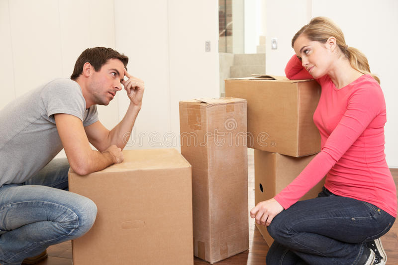 Young couple looking upset among boxes royalty free stock images