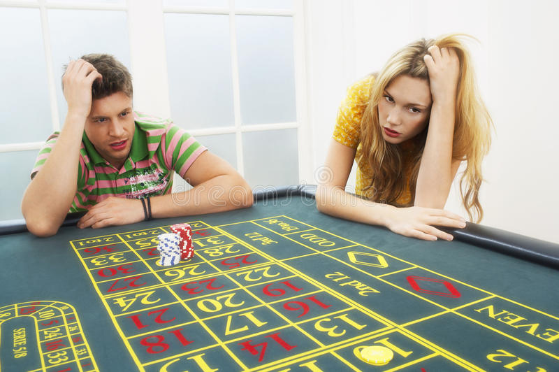 Young Couple Losing On Roulette Table royalty free stock photography
