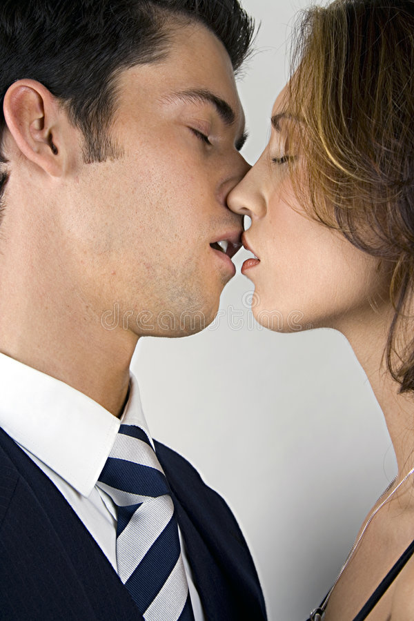 Young Couple In Love. Portrait of a young couple in their mid-twenties, preparing to kiss with eyes closed and upper lips touching. Isolated on white background