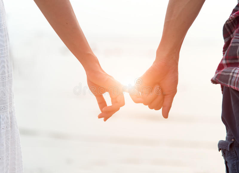 Young couple in love, Attractive man and woman enjoying romantic evening on the beach, Holding hands watching royalty free stock image