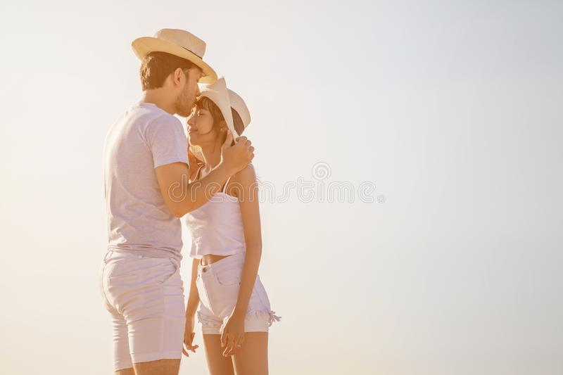 Young couple in love at beach . boyfriend kissing  girlfriend  on the forehead . happy .Romantic  in sunset outdoor. asian . stock photo