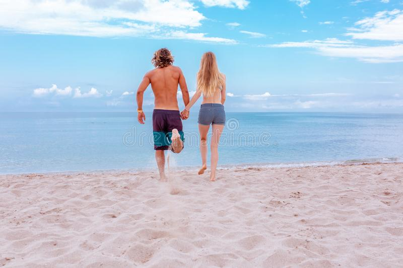 Young couple in love at beach and enjoying time being together, running on the beach.  stock photo