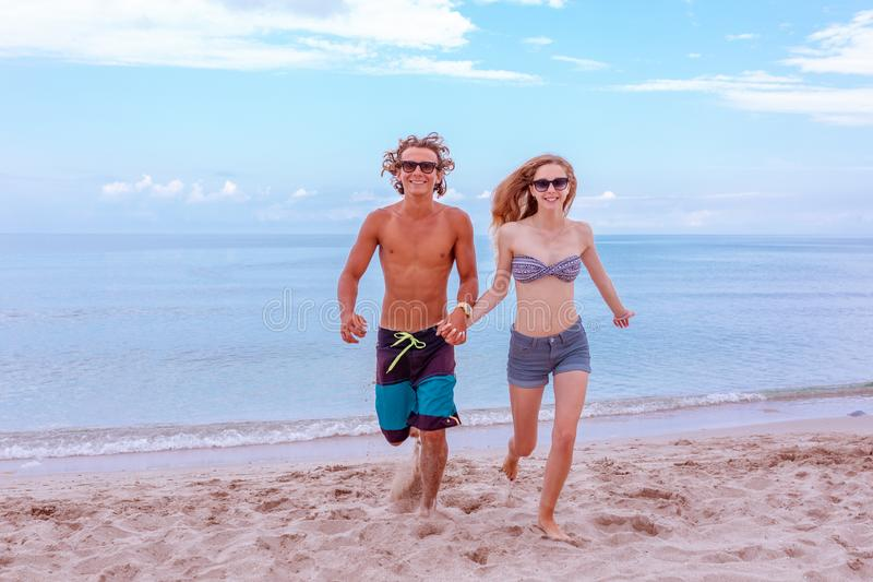 Young couple in love at beach and enjoying time being together, running on the beach.  royalty free stock photo