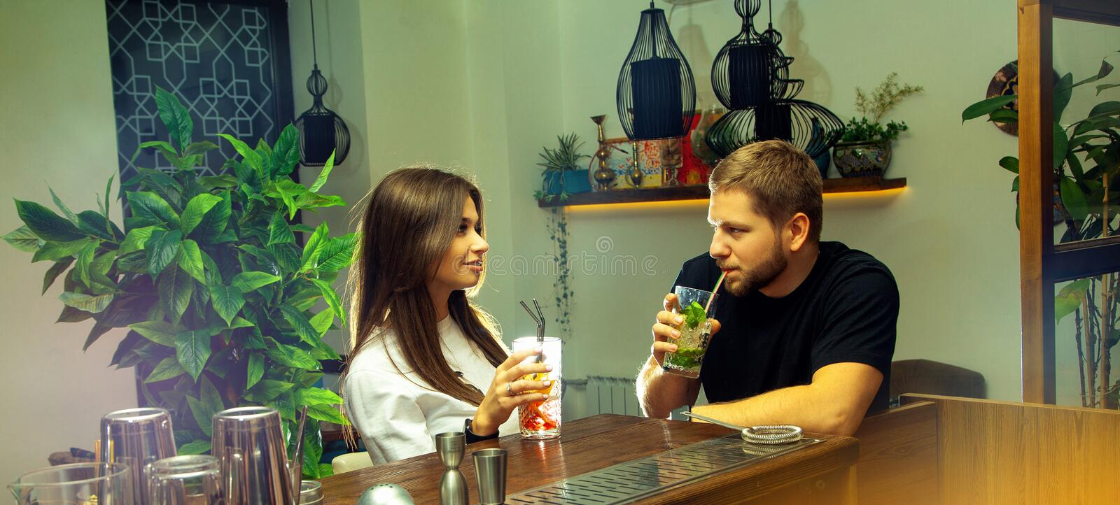 Young couple in love drinks cocktail and flirting. Horizontal photo of young couple in love drinks cocktail and flirting at the bar table stock photo