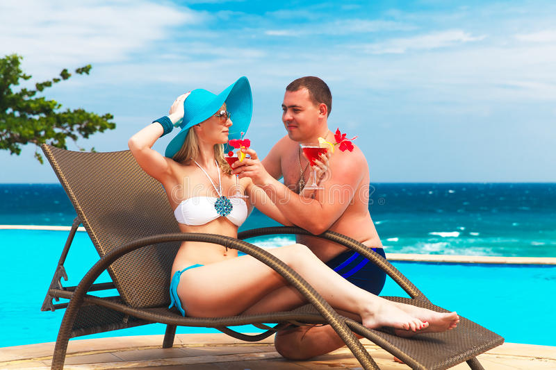 Young couple in love is enjoying cocktails at the poolside. Tropical sea in the background. Summer vacation. stock photos