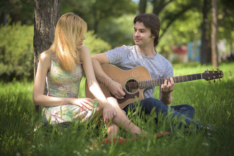 Young couple in love enjoying a sunny day. Gorgeous young couple laughing and enjoying each other's company Man playing a guitar, singing a song to his beloved stock images