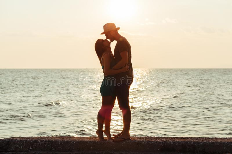 Young couple in love enjoying sunset on the beach royalty free stock image