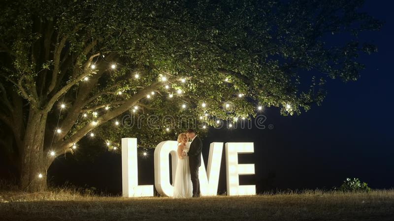 Young couple in love in evening dresses are dancing near love light letters. Luxury couple in evening dresses are dancing and hug on the nature near a big stock photo