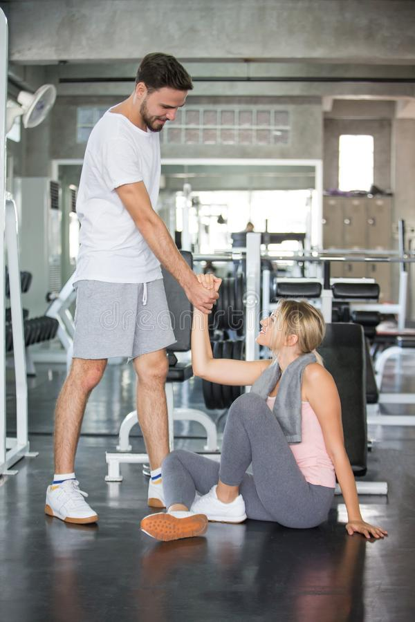 young couple in love exercise together in fitness gym . sport man boyfriend helping girlfriend to stand up or get up from floor. stock photography